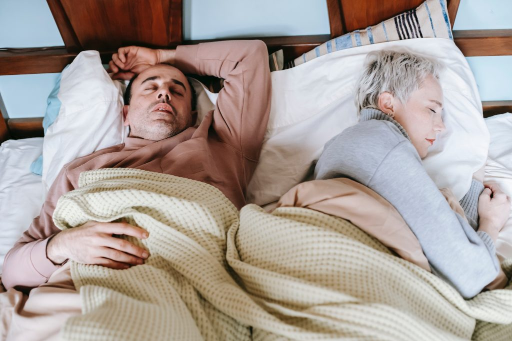 man and woman asleep on bed.