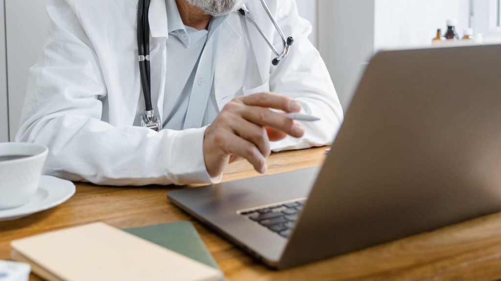 Doctor in white lab coat points at laptop screen.