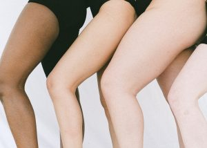 three women stand close to each other, with their legs bent to show their skin.