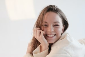 a young woman smiles with her hand pressed to her face.